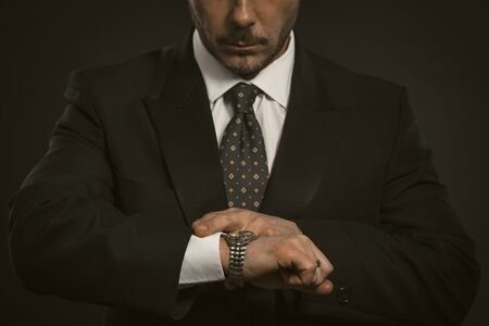 Businessman checking time on his wrist watch. Close up portrait of business man looking at clock on hand. Front view of serious bearded man in black suit.