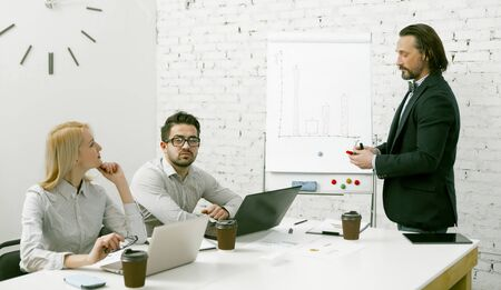 Attractive businessman standing near a white board presents to the team his business idea. Colleagues carefully listen to speaker sitting at the office table. Teamwork in office concept.