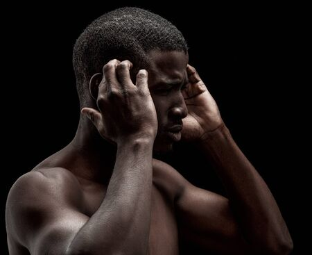 Afro-American man feels headache or stress. Profile portrait of naked dark-skinned man expressing exhaustion. He massages his head with hands isolated on black background. Stok Fotoğraf
