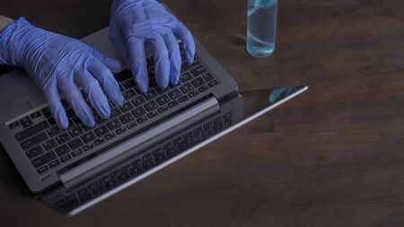 Hands in gloves typing on the laptop keyboard. Necessary preventive measure in the fight against the coronavirus. Pandemic lifestyles concept. 免版税图像