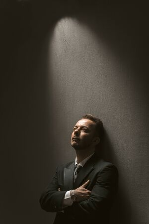 Thoughtful businessman stands crossed arms. Well dressed handsome man in black formalwear standing alone against dark grey background.