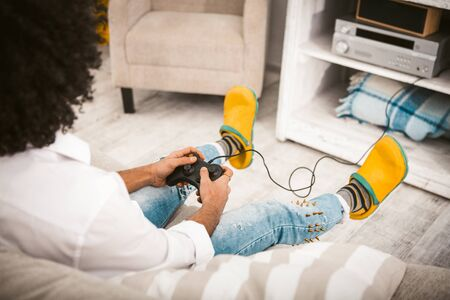 Young man playing computer game. Gamer Remove the buttons on the joystick from the PlayStation in cozy home interior. Guy in casual have fun self-isolation period. High angle view.