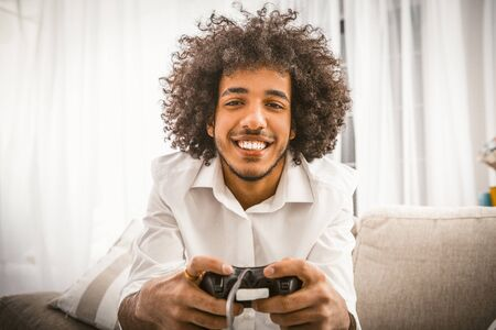 Arabic gay playing computer game. Young man holds Play Station joystick sitting at sofa in backlit. Smiling handsome looking at camera. Funny self-isolation concept. Foto de archivo