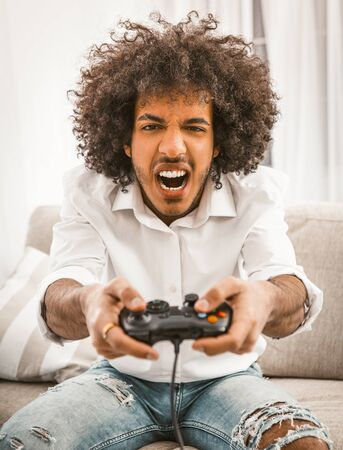 Screaming gamer shoots or attacks in computer game. The concept of emotions. Young Arab playing computer game sitting at sofa in home interior.