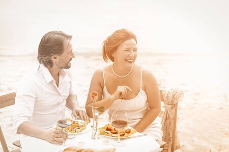 Happy adult couple made a romantic date on the beach. A man and a woman drink wine and eat together while sitting at a table near the water outdoor. The woman is laughing happily. Toned image. Фото со стока