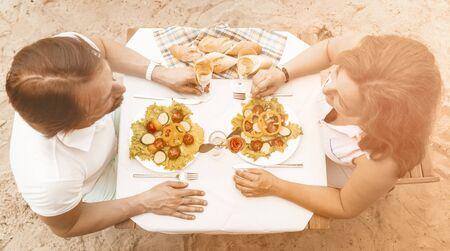 Couple amoureux d'âge moyen assis à une table avec salade et verres de vin blanc sur une plage de sable, homme heureux et femme se regardant, vue grand angle, image tonique. Banque d'images