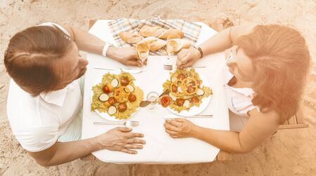 Middle-aged couple in love sitting at a table with salad and glasses of white wine on a sandy beach, Happy man and a woman looking each other, High angle view, Toned image.