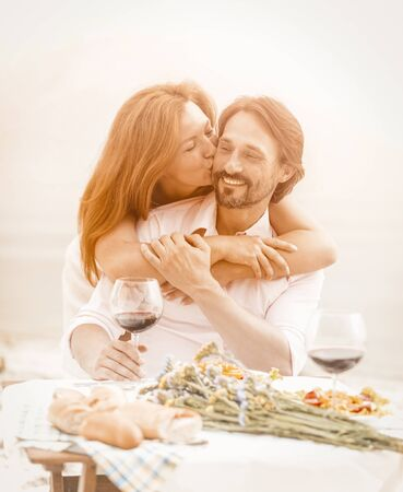 Happy middle-aged couple resting in a beach cafe, a beautiful woman tenderly kisses her man hugging his shoulders, a man and a woman eat and drink wine in the fresh air. Toned image.