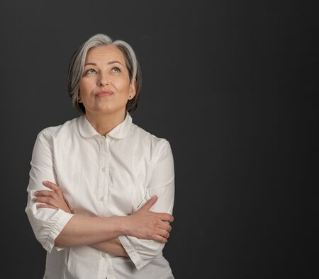 Creative mature woman looking upward thoughtfully with her arms crossed. Charming silver-haired woman smiling tenderly on dark grey background with textspace at right side.