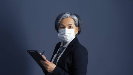 Confident middle-aged businesswoman in protective mask using digital notepad. Graying female model looks at camera, isolated on gray background in studio. Toned image.