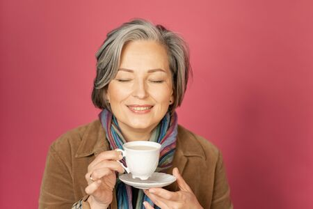 Charming mature woman enjoys by cup of coffee closing her eyes. Happy gray-haired lady drinks coffee posing on pink background in the studio. Close up portrait with text space on right. 스톡 콘텐츠