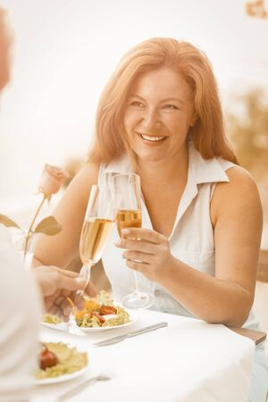 Happy woman holds glass of white wine smiling while looking to her husband. Mature caucasian couple celebrates wedding anniversary while sitting in cafe outdoors near sea. Toned image.