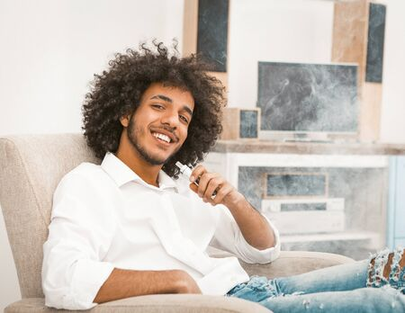 Young freelance man relaxes while smoking e-cigarette. Shaggy macho charmingly smiles while looking at the camera. Toned image.
