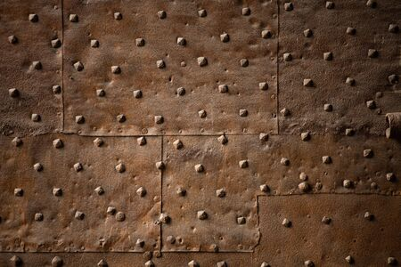 Old wall covered with sheets of rusty iron with rivets. Abstract retro background.