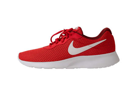 Red sneakers of Nike brand. Shoes with laces for jogging and fitness. Stylish youth model. Object cut out on white background. Side view. May, 2019. Kiev, Ukraine. Redactioneel