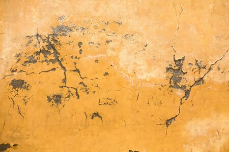 Grunge plastered wall with cracks. Yellow color retro stucco. Close up shot. Abstract texture or background. Banco de Imagens