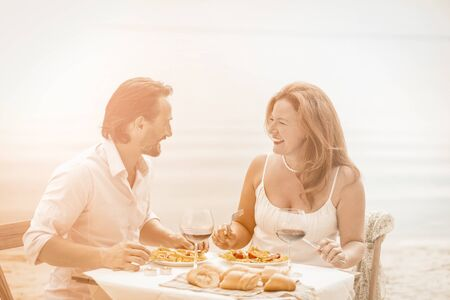 Romantic people spend time together by sea background. Happy Caucasian couple resting in beach cafe on sunny summer day. Tinted image.