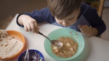 Preschool child learns to eats soup himself sitting at domestic kitchen table. Healthy home food concept. Top view.