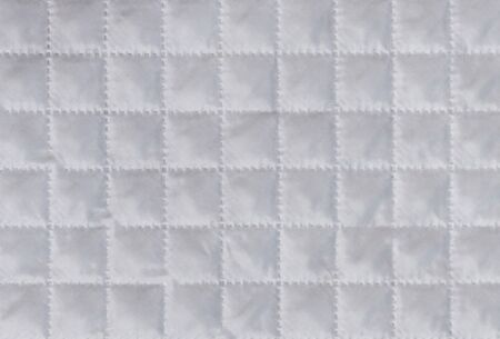 White cloth or material texture with checkered structure or embossing. Synthetic fabric pattern or background. Macro, close up shot.