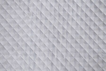White textile texture with checkered mesh embossing. Abstract fabric pattern, background or empty blank.