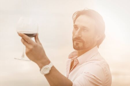 Handsome Caucasian man with glass of red wine on white background. Holiday or festive toast concept. Tinted image.