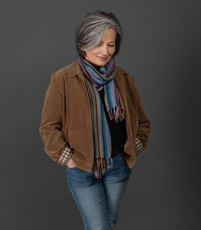 Creative gray-haired woman in casual on gray, portrait. Lady in jacket, colorfull scarf and jeans smiles looking down while standing hands in pockets.