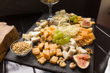 Cheese assorted or cheeseboard. Gourmet cheeses with fig, green grapes and nuts on black wooden plank. Focus on parmesan with almonds in the center of image.