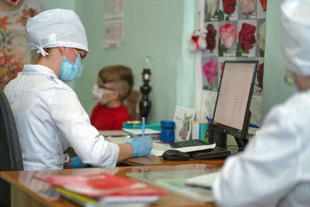 Doctor makes notes on card of little patient after examination, recording appointment and results. Masked woman and boy due to virus outbreak and pandemic. City Hospital. May, 2020, Brovary, Ukraine. Redactioneel