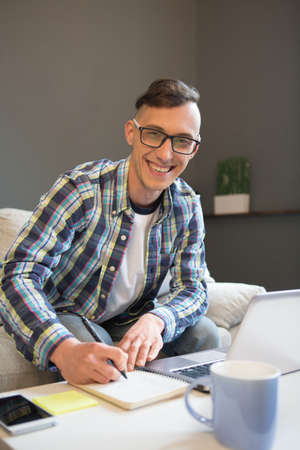 Remote work concept, home office. Close up view of smiling young man working on freelance out of the office. 免版税图像
