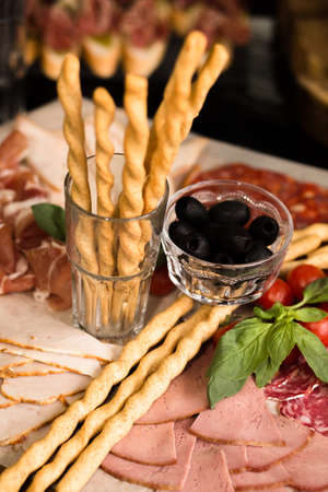 Prosciutto and meat assorted. Breadsticks with meat slicing. Close up shot. Holiday or event treats. Catering food concept. Reklamní fotografie