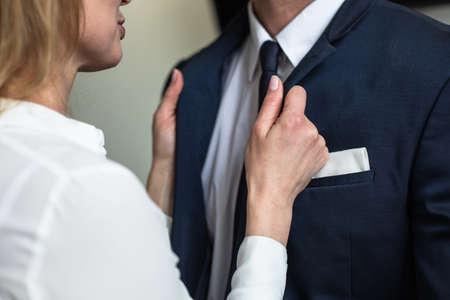 Caucasian woman straightens businessman's collar. Passionate flirting business people. Love affair in office. Close up shot. Foto de archivo