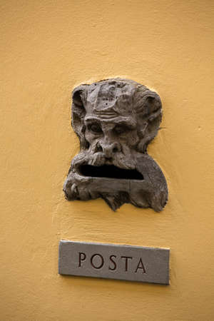 Vintage mailbox gap on old building wall. Slot with inscription POSTA or Mail on metal plate and bizarre head of unrecognizable creature. Stock fotó