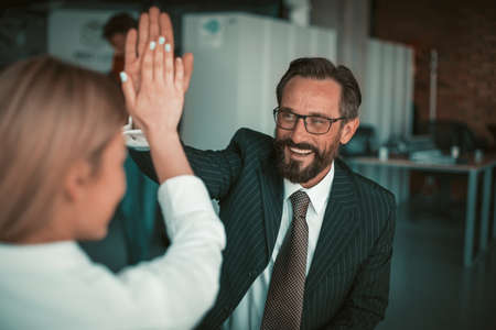 High five gesture from businesspeople in office. Happy caucasian man and blonde woman stand with hands joined in joyful gesture. Celebration of success in business. Achievement concept. Tinted image.