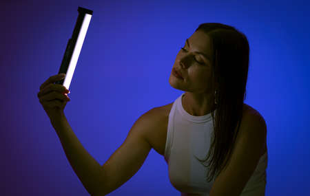 Young woman holds LED lamp posing on blue background. Female model at presentation of Nanlite Studio LED Lighting. Backstage. June 2020, Kiev Ukraine.