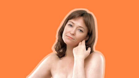 Anti-aging skin care concept. Beauty mid aged woman touches cheek with hand looking at camera. Caucasian model with bare shoulders isolated on orange background. Empty space for text.