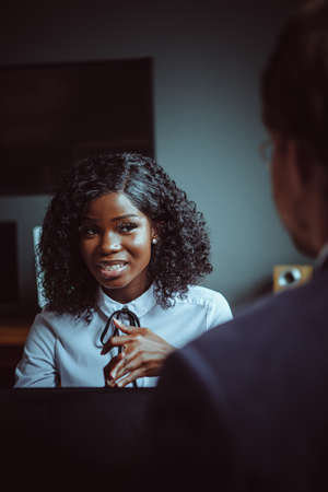 Charming African business woman listens to his male colleague sitting with his back in foreground. Young African American girl portrait. Business meeting concept. Tinted image.