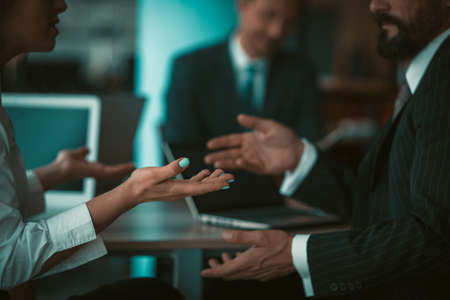 Businessman and businesswoman gesturing with hands while conversation during meeting in office. Sign language concept. Close up shot. Tinted image.