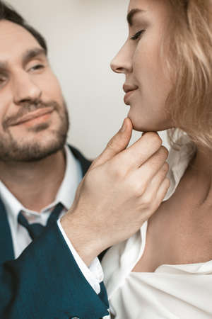 Passionate couple in the office at the workplace. Man holds a girl by the chin. They smile . High quality photo.