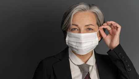 Pretty gray-haired middle-aged business woman putting on protective mask and showing ok or okey sign while posing on gray wall background. Quarantine concept. Stock fotó