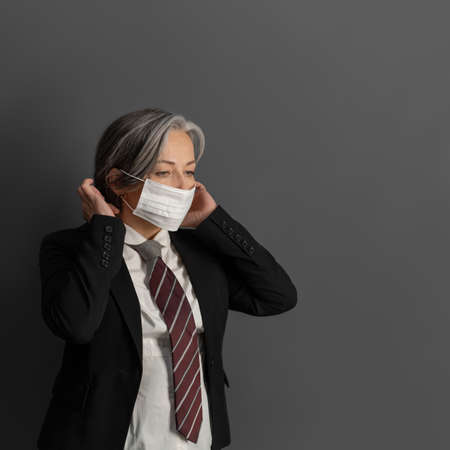 Elegant mature businesswoman putting on protective mask. Serious female office worker on gray back. Coronavirus pandemic concept.