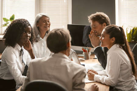 Funny business meeting in office. Office workers confer at their desks and smile. High quality photo. Banco de Imagens
