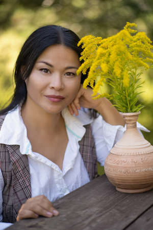 Beauty Asian woman with yellow flowers resting outdoors. Young brunette sits at wooden table with bouquet of Solidago or Canada Goldenrod on it. Romantic female portrait. 免版税图像
