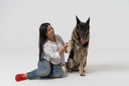 Smart dog gives paw to owner. Pretty woman and Eastern European Shepherd isolated on white background. Pet concept. Studio shot.