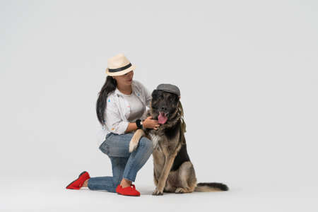 Woman in hat and Eastern European Shepherd wearing cap posing on white background. Pet concept.