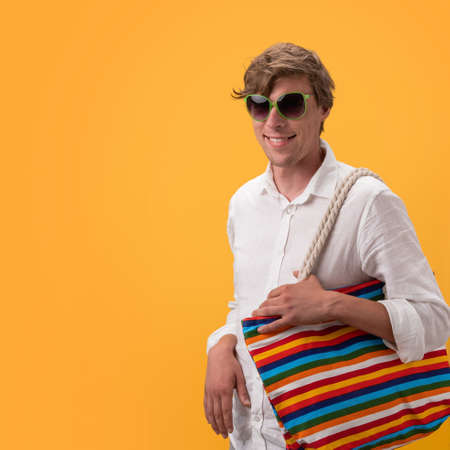 Young funny man with large multicolored bag rejoices looking throught sunglasses. Cut out on yellow background. Shopping concept. Vacation concept.