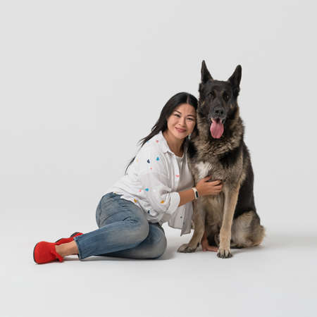 Beautiful woman hugs thoroughbred Shepherd dog. Happy brunette sitting with dog pet on floor. Cut out on white background.