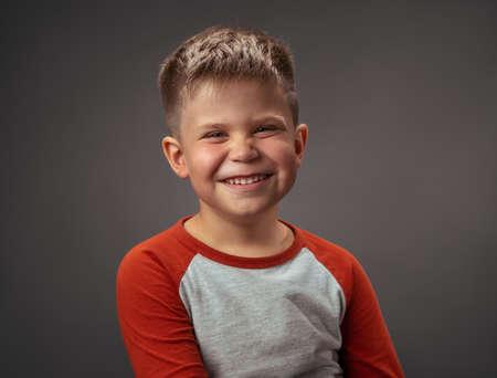 Happy preschool boy expresses joy. Smiling broadly child cut out on gray. Studio portrait. Emotions concept. 免版税图像