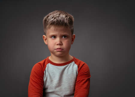 Sad boy looking at camera. Preschool kid expresses emotions. Isolated on gray background. Conflict concept. Copy space at right.