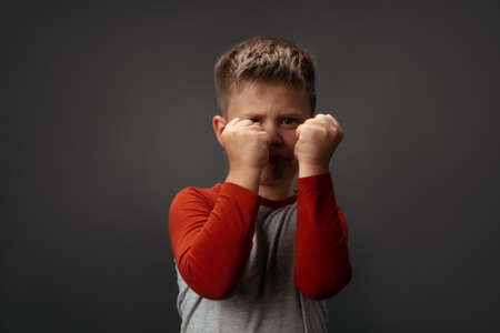 Sad preschool kid expresses anger. Little boy holds his fists in front of him to attack or defend. Conflict concept. Fight concept.
