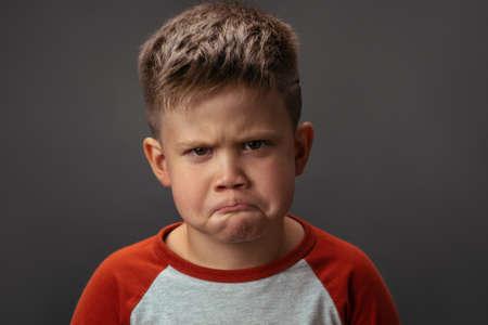 Preschool boy expresses sad emotions. Conflict concept. Close up portrait.